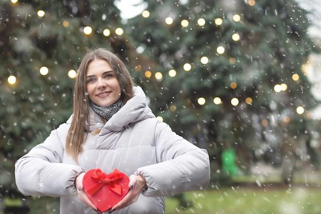 Encantadora mujer rubia sosteniendo una caja de regalo en la calle durante las nevadas. espacio vacio
