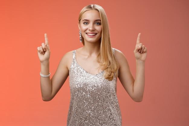 Encantadora mujer rubia tierna femenina en vestido de fiesta plateado levante las manos apuntando hacia arriba sonriendo encantado recomendar servicio de productos cosméticos impresionantes, de pie felizmente sonriendo fondo rojo.