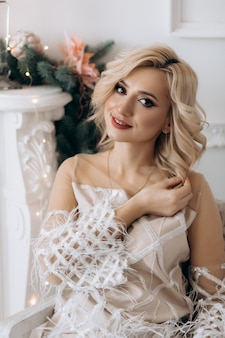 Encantadora mujer rubia con vestido blanco posa en una habitación con un gran árbol de navidad