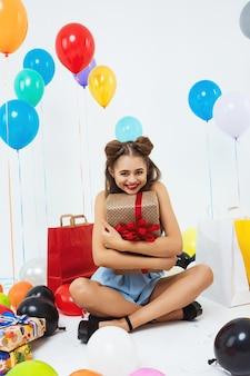 Encantadora mujer sentada en posición de loto con gran caja de regalo