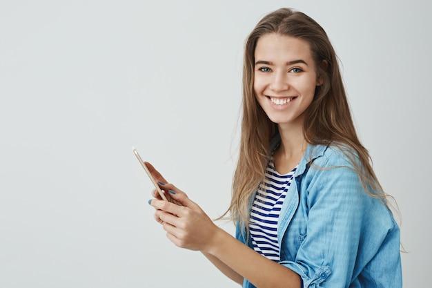 Encantadora mujer sonriente feliz que sostiene la tableta digital que disfruta usando el dispositivo nuevo