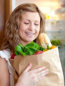 Encantadora mujer sosteniendo una bolsa de supermercado
