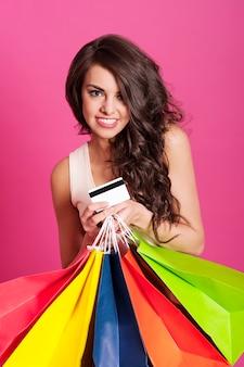 Encantadora mujer sosteniendo bolsas de compras y tarjeta de crédito