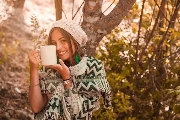 Encantadora mujer con taza en el bosque