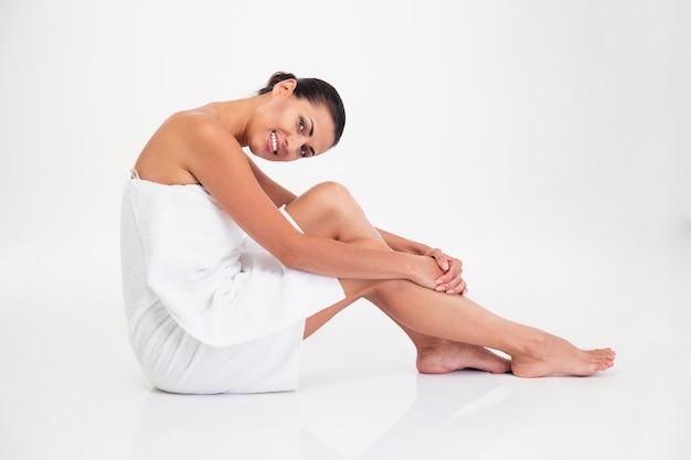 Encantadora mujer en toalla sentada en el suelo