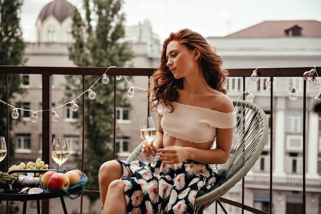 Encantadora mujer en traje floral sostiene copa de vino y descansa en la terraza