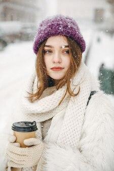 Encantadora mujer en traje de invierno pasando tiempo libre al aire libre y bebiendo café recién hecho.