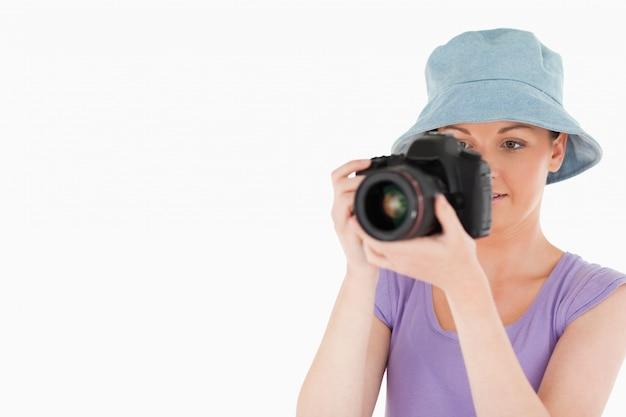 Encantadora mujer usando una cámara mientras está de pie