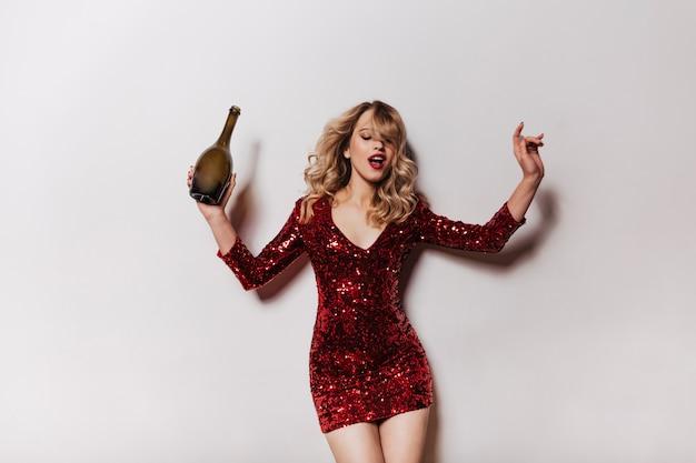 Encantadora mujer en vestido corto de brillo bailando en la pared