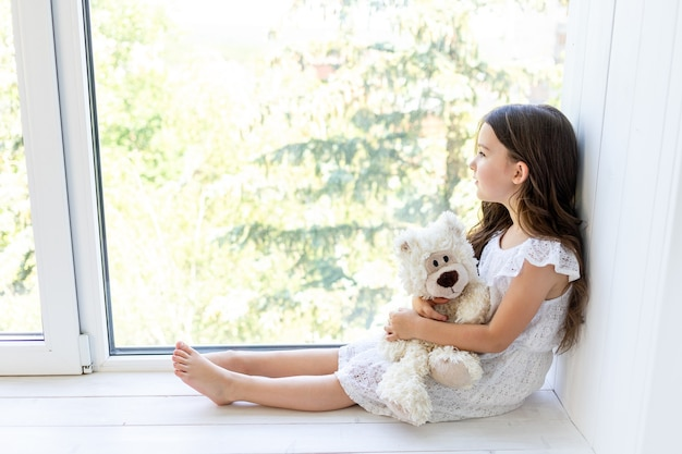 Encantadora niña de 5-6 años abraza a un oso de peluche y mira por la ventana