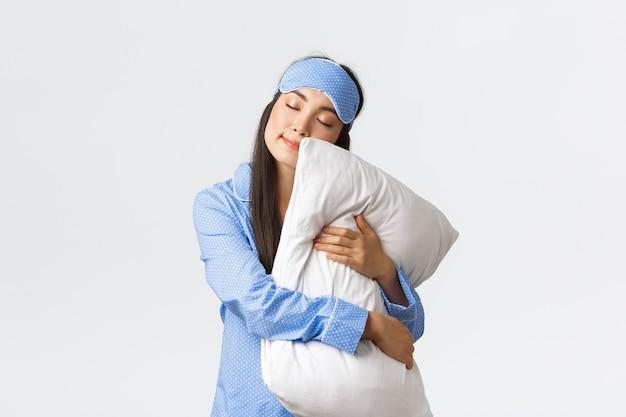 Encantadora niña asiática durmiendo en antifaz y pijama, abrazando la almohada y acostada con los ojos cerrados, soñando, durmiendo por la noche, posando sobre fondo blanco de ensueño. copia espacio