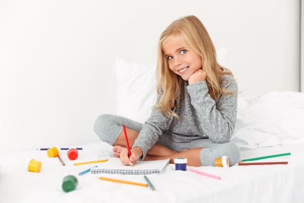 Encantadora niña dibujando con lápices sobre cama blanca