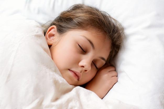 Encantadora niña durmiendo en una cómoda cama cubierta con una manta suave y cálida