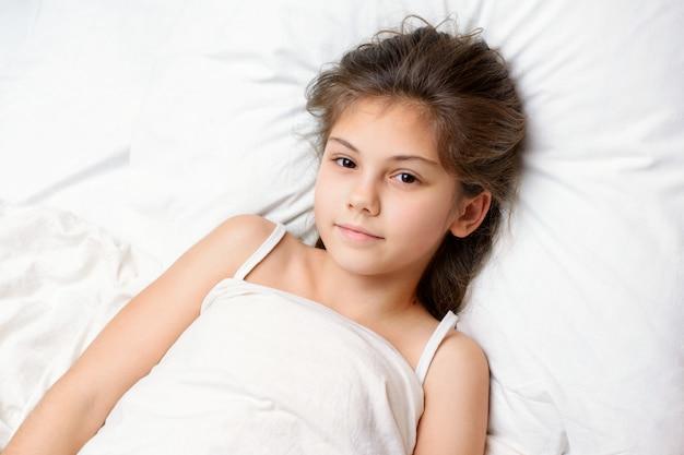 La encantadora niña se ha despertado temprano en la mañana llena de poder con un deseo ardiente de ir a la escuela y estudiar. hermosa niña pequeña se encuentra en una cama cómoda