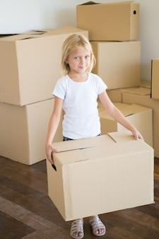 Encantadora niña llevando caja de cartón y mirando a cámara