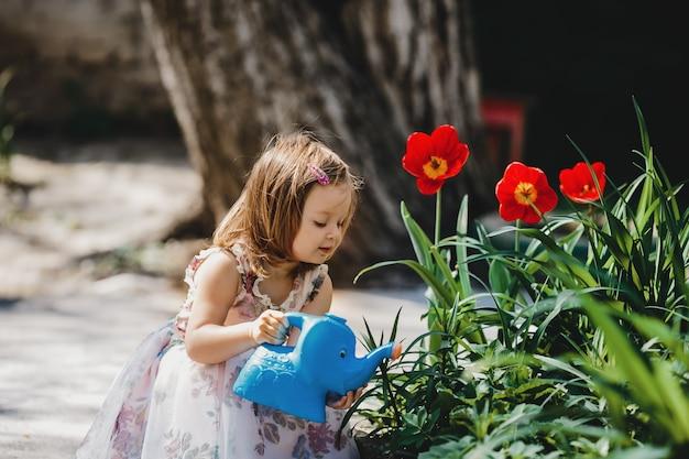 Encantadora niña se ocupa de las flores en el jardín