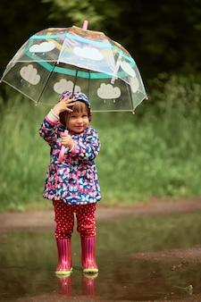 Encantadora niña con paraguas se divierte de pie en botas de goma en la piscina después de la lluvia