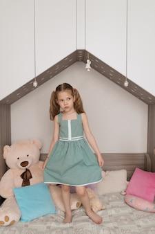 Encantadora niña de pie en la cama de su habitación