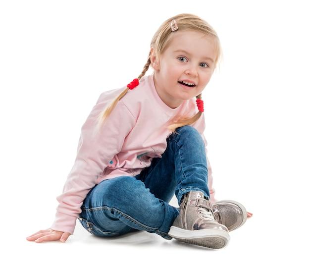 Encantadora niña sentada en el piso
