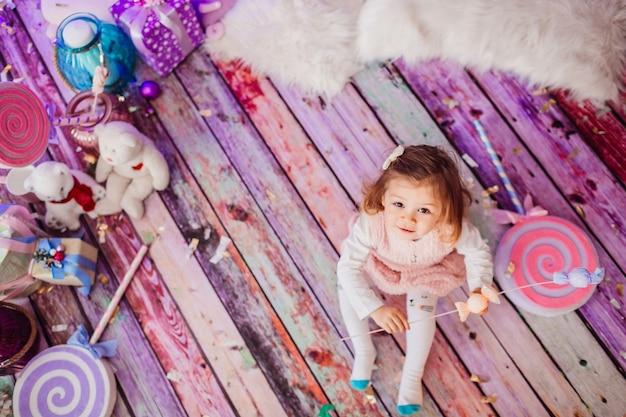 Encantadora niña se sienta en el piso de color rosa entre los juguetes de peluche