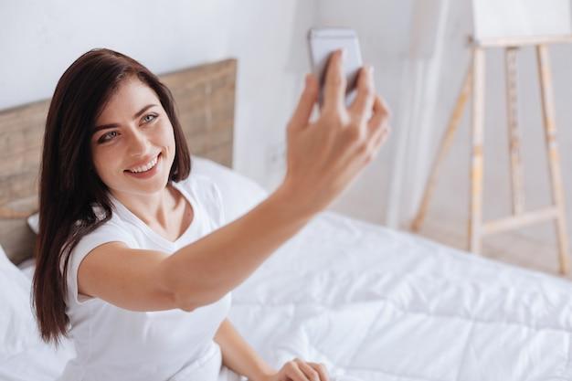 Encantadora niña sonriendo mientras está sentada en una cama y fotografiarse con un teléfono por la mañana