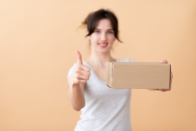 La encantadora niña sostiene una caja de manualidades en la mano y muestra la clase con el pulgar hacia arriba en el espacio beige.