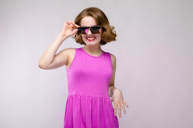 Encantadora niña con vestido rosa en gris alegre niña con gafas cuadradas la niña ajusta las gafas