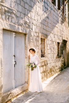 Encantadora novia se encuentra cerca de una pared de ladrillos