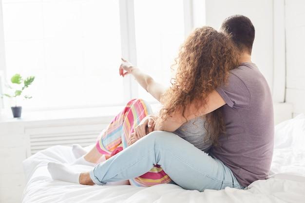 Encantadora novia y novio vestidos casualmente, disfrutan de la intimidad y la unión, posan en la cama en el dormitorio, miran la ventana, tienen una conversación agradable, expresan buenos sentimientos el uno al otro. concepto de la hora de dormir