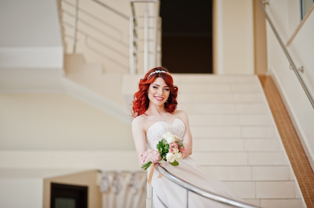 Encantadora novia pelirroja con ramo de novia