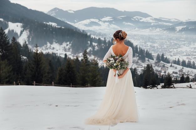 Encantadora novia posa con un rico ramo de novia en las montañas de invierno
