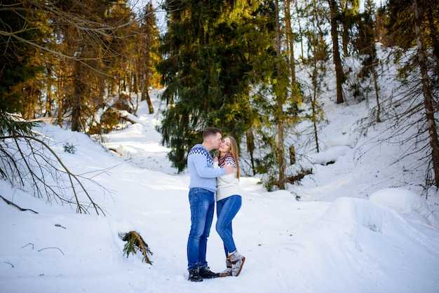 Encantadora pareja abrazándose en el bosque de invierno.