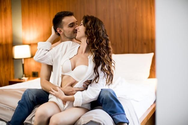 Encantadora pareja abrazándose en la cama en casa