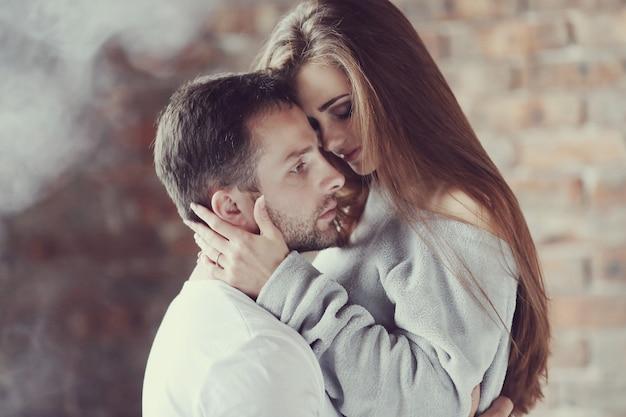 Encantadora pareja abrazándose en casa