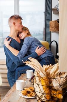 Encantadora pareja abrazándose en la cocina