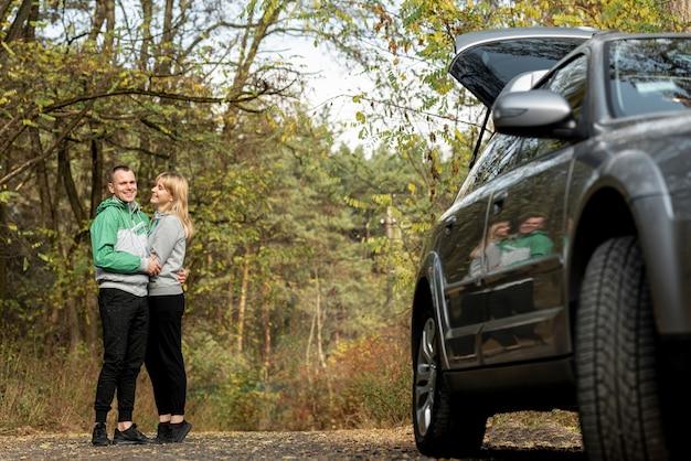Encantadora pareja abrazándose detrás de un auto