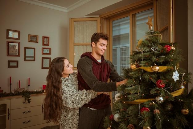 Encantadora pareja abrazándose mientras decoraba el árbol de navidad