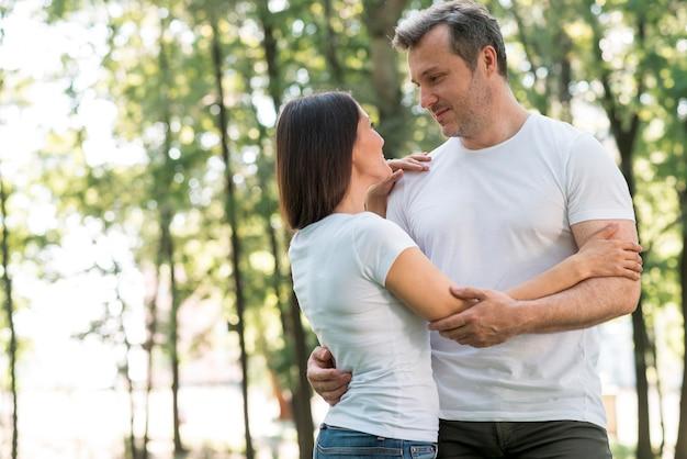 Encantadora pareja abrazándose y mirándose en el parque