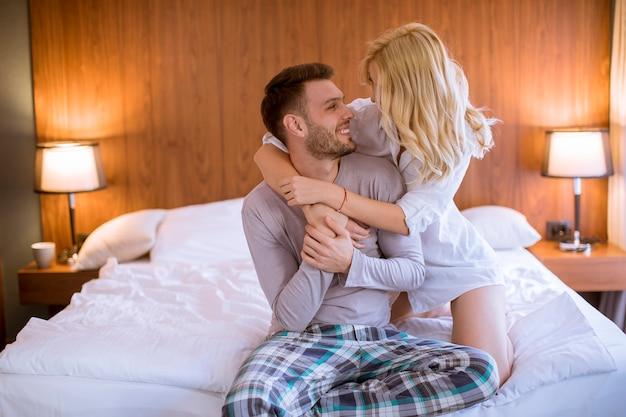 Encantadora pareja abrazándose en su cama en casa