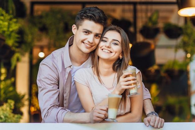 Encantadora pareja abrazándose en la terraza de verano de la cafetería moderna y beber café con leche.