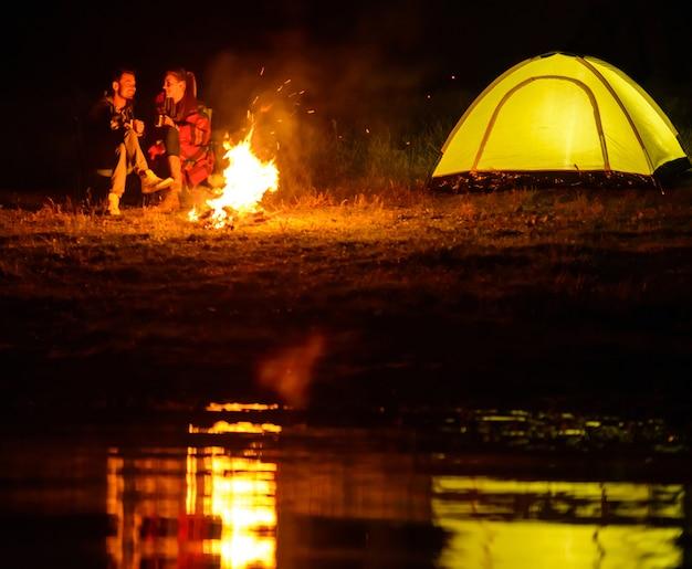 Encantadora pareja, acampando, sentada alrededor de la fogata.
