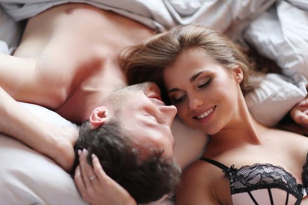 Encantadora pareja acostada en la cama