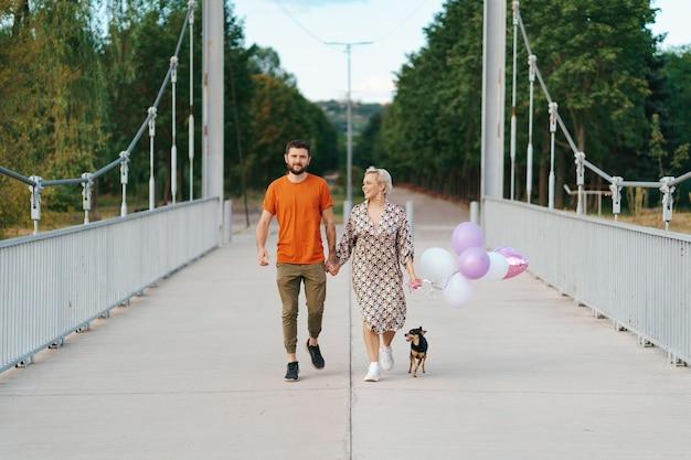Encantadora pareja alegre caminando feliz en el puente con su perro y globos rosados sonriendo
