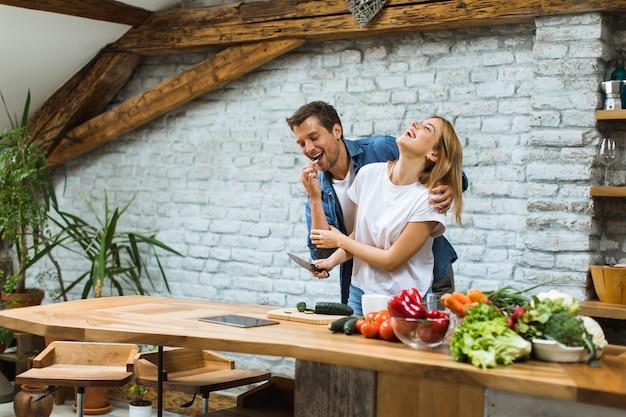 Encantadora pareja alegre que cocina la cena juntos y se divierte en la cocina rústica