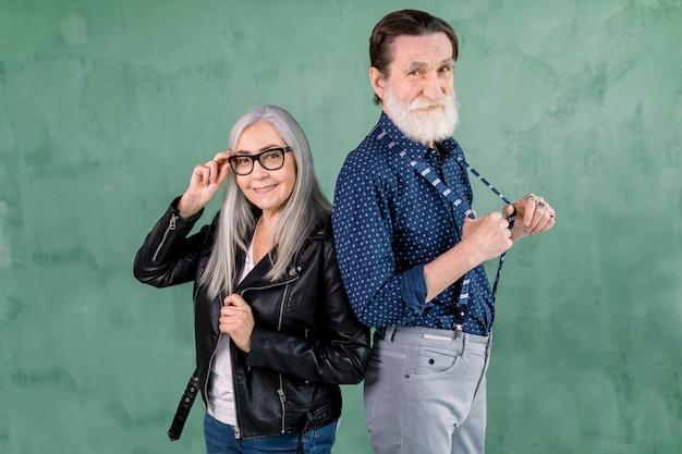 Encantadora pareja alegre sonriente senior, hombre guapo con barba y mujer de pelo gris, posando a la cámara frente a la pared verde. mujer tocando sus lentes