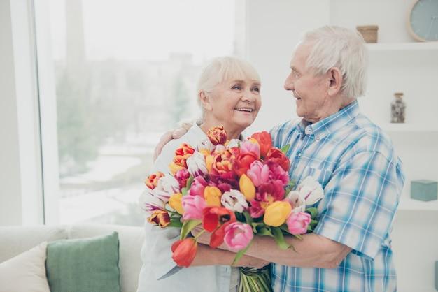Encantadora pareja de ancianos posando juntos en el interior