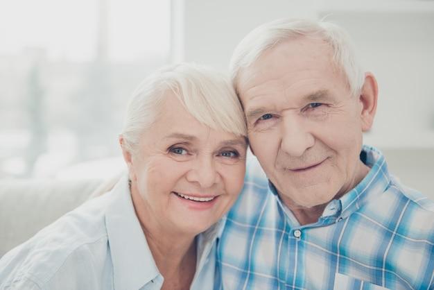 Encantadora pareja de ancianos posando juntos en el sofá