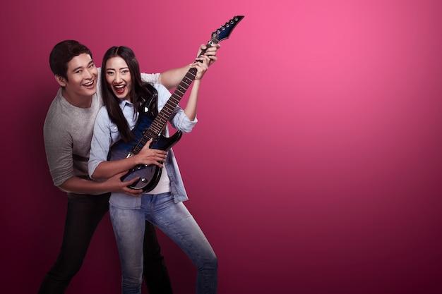 Encantadora pareja asiática tocando la guitarra