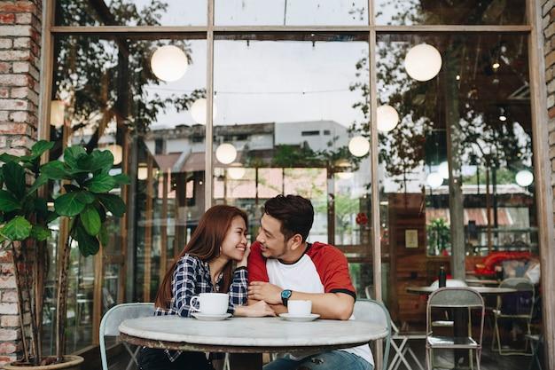 Encantadora pareja asiática tomando un café