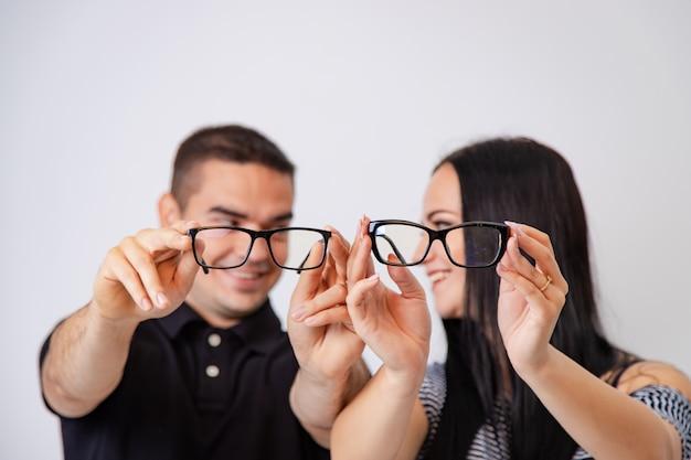 Encantadora pareja atractiva sentados juntos y mirando unos a otros tienen gafas en sus manos. pareja joven sonriendo el uno al otro mostrar anteojos